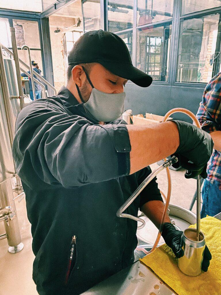 Chico con traje color negro, gorra y guantes negros, cubrebocas color gris, sirviendo una cerveza en una lata.