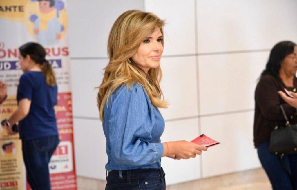 Gobernadora de Sonora con blusa de mezclilla azul y con un folleto color rojo en las manos.