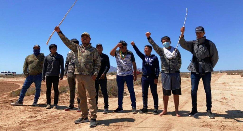 Grupo de 9 hombres con la mano arriba. El hombre al frente del grupo tiene una chamarra camuflaje y pantalon color crema.