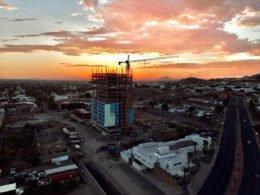 Ciudad de Hermosillo con construcciones y casas. De fondo se nota un atardecer de color naranja-rosa.