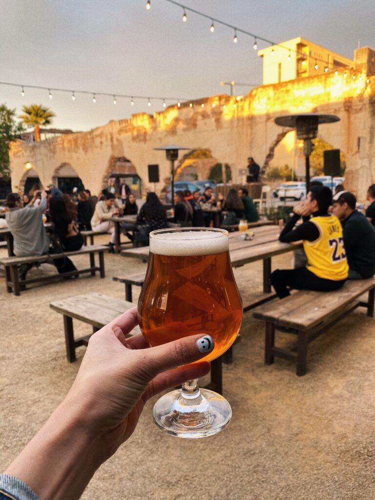 Mano izquierda con la uña pintada del dedo pulgar color azul claro con una cara feliz. La mano deteniendo una copa de cerveza dorada.