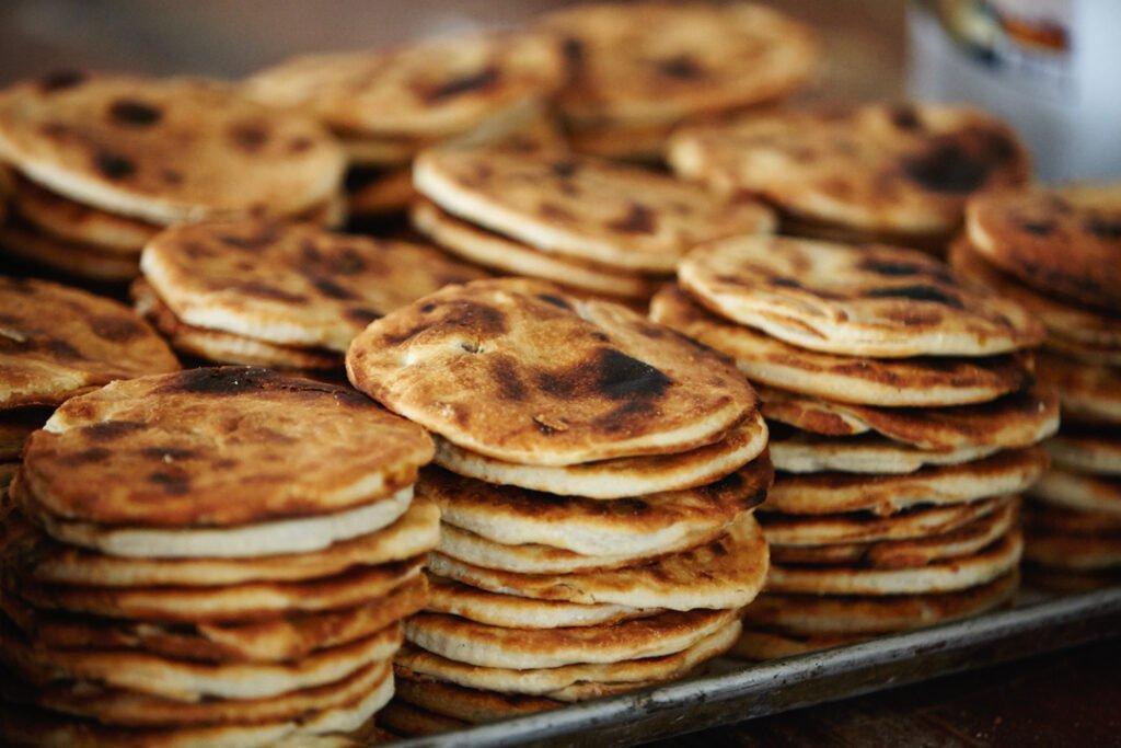 Coyotas recien horneadas tipo empanadas en una charola de acero inoxidable.