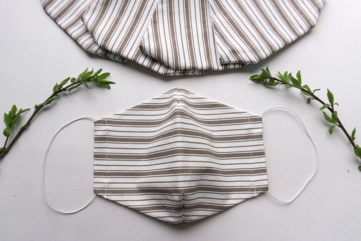 Cubrebocas de tela blanco con café sobre una mesa blanca