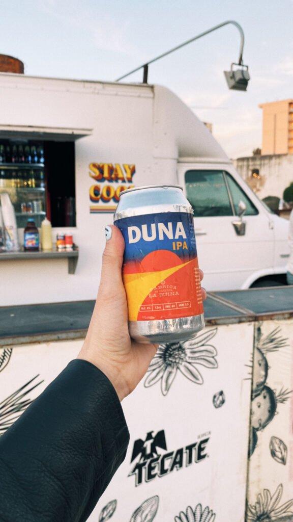 """Mano con una lata de cerveza color plateada con etiqueta color azul, naranja y rojo. En la parte de arriba con letras color blanco """"DUNA"""" y abajito de esto IPA con letras color naranja."""