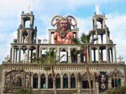 Casa estilo gotico con una escultura de un hombre color roja, barba y cabello largo color cafe y cuernos de fauno.
