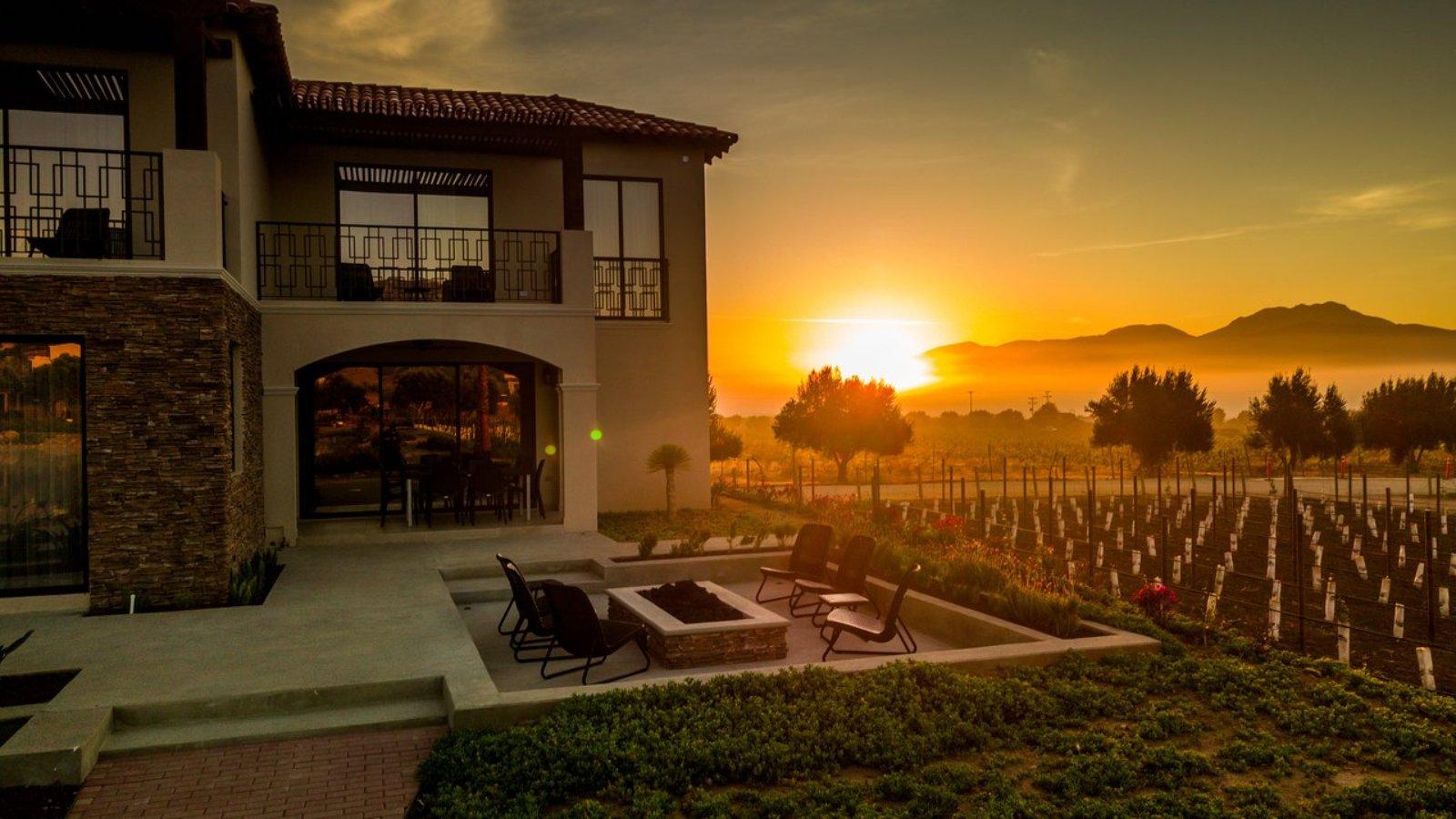 Casa color crema a un lado de viñedo junto a un atardecer naranja. Viñedos del valle de guadalupe