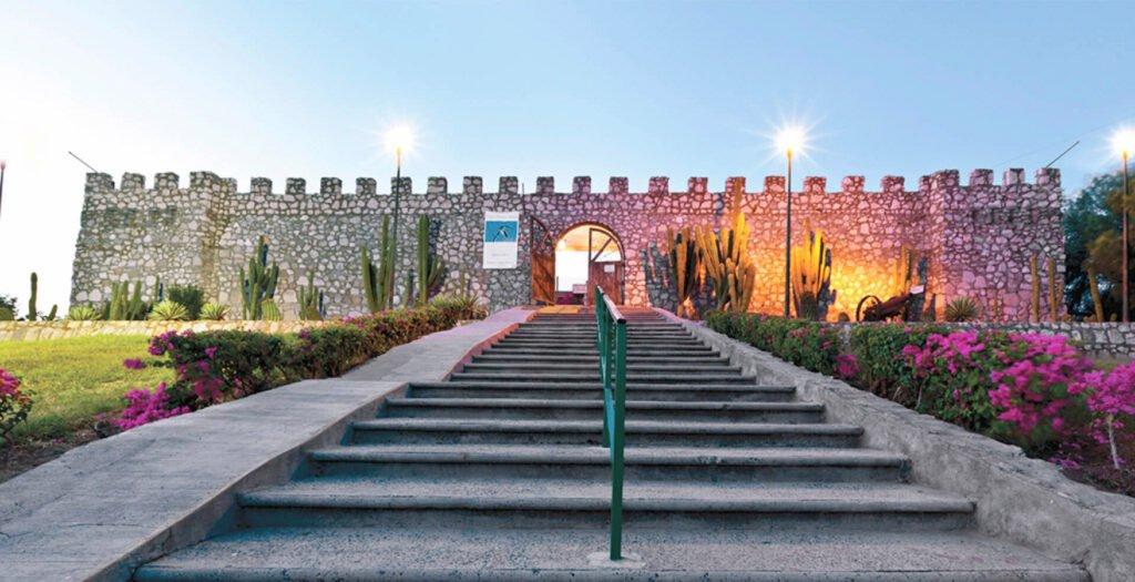Estructura de piedra tipo castillo con cactus gigantes a los lados. Saliendo del edificio se encuentra una escalera de cemento con barandal color verde. Por los lados buganvilias chicas color rosa mexicano.