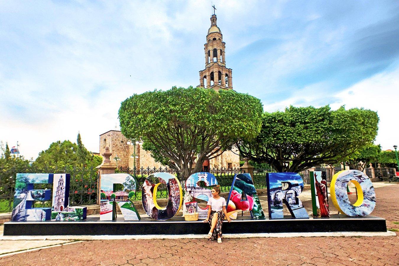 """Plaza con letras que dicen """"El Rosario"""" de diferentes colores e imagenes. En esta letras gigante se encuentra una chica con falda color negra y blusa blanca."""