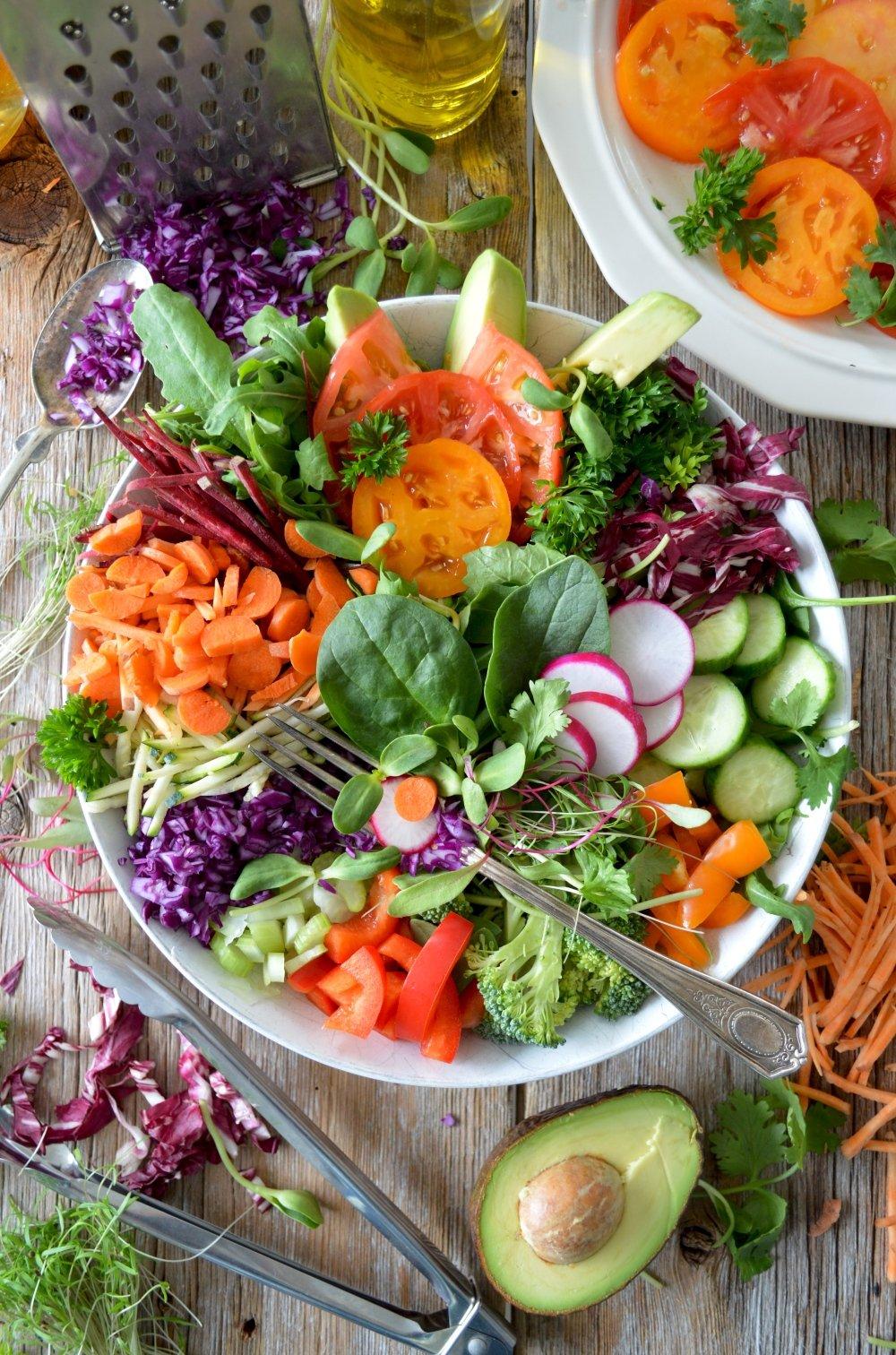 plato blanco con ensalada de verduras de colores sobre una mesa de madera