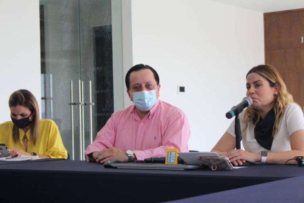 Tres personas sentadas en una mesa. Del lado izquierdo se encuentra una señora con blusa color amarilla y cubreboca color negro. En medio se encuentra un señor con camisa color rosa y cubreboca color blanco. Y del lado derecho se encuentra una señora con blusa color blanca y pañuelo negro, hablando por un micrófono.