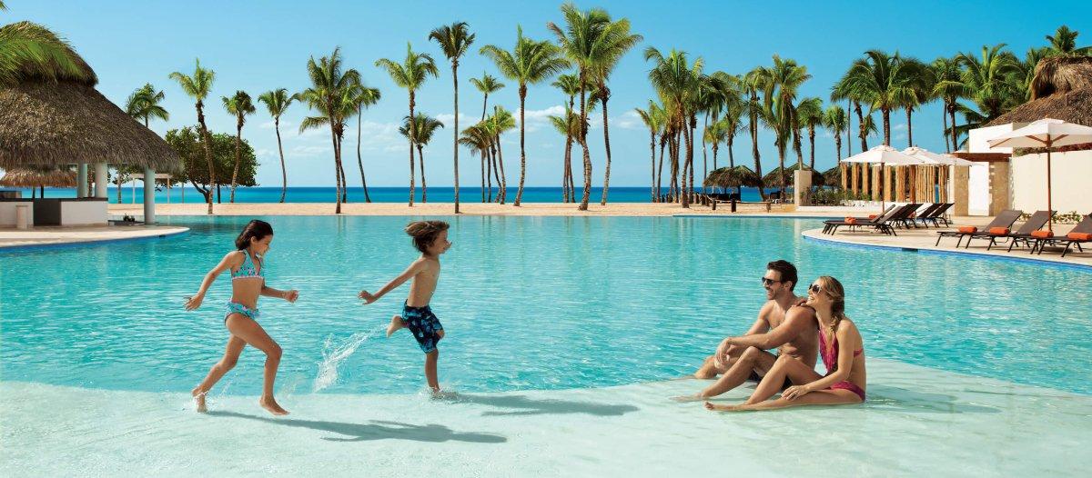 niña y niño corren a la orilla de la piscina donde etsán sentados dos adultos, detrás hay palmeras y el mar