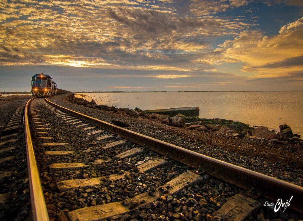 Vias del ferrocarril de Empalme que se encuentra a un lado del mar, al fondo un tren con luces prendidas. El cielo con nubes hermosas color blancas con reflejos del sol color naranja-amarillo.
