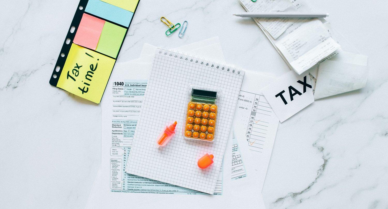 finanzas personales; libreta con calculadora encima de color naranja, post-its de colores a un costado y del otro lado un letrero que dice TAX