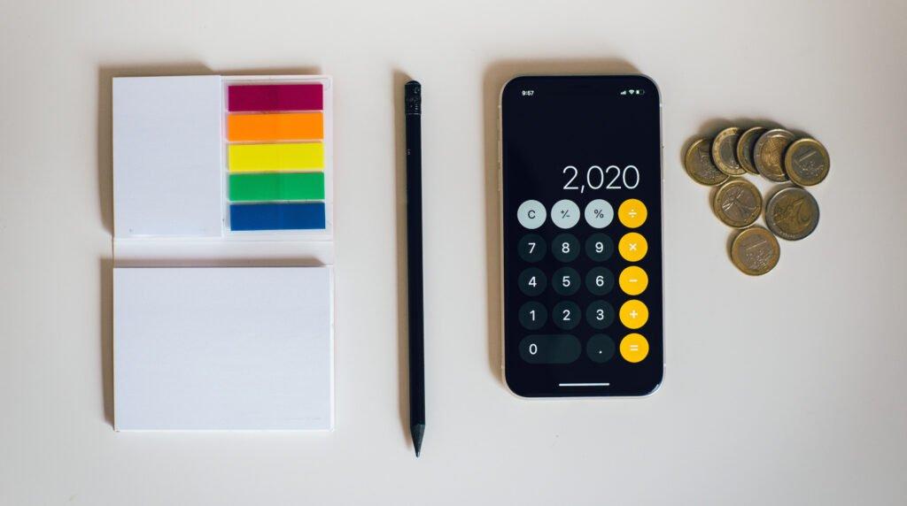 """post its de colores, un bolígrafo, una calculadora con la cifra """"2,020"""" y unas monedas en el costado derecho"""