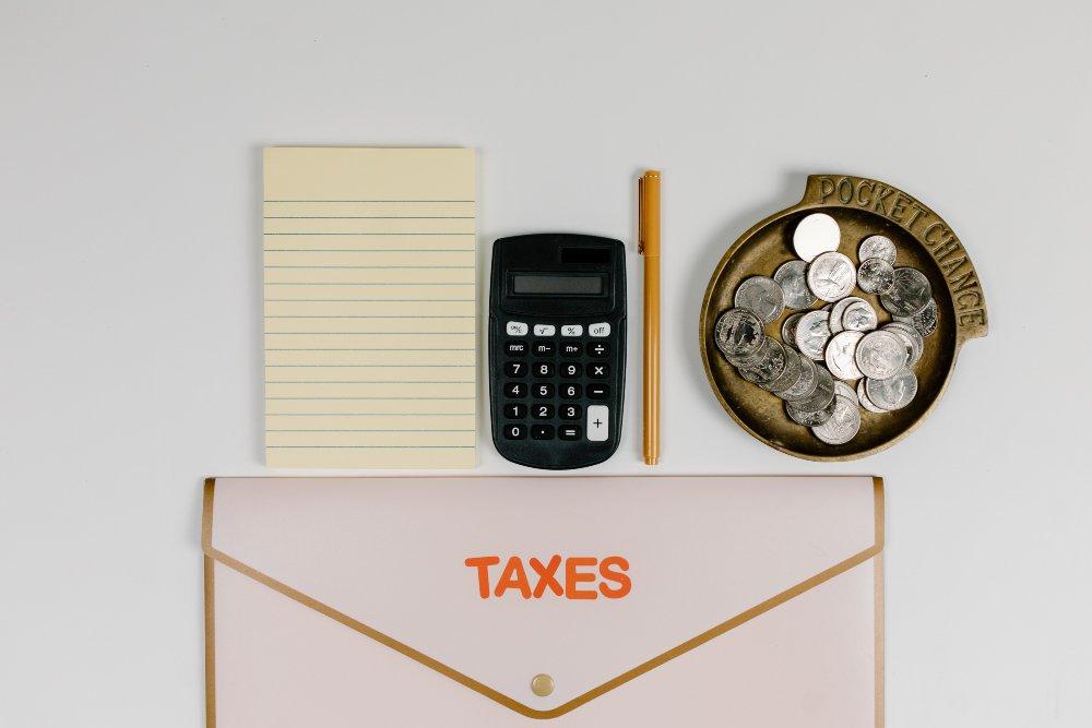 sobre que dice TAXES, bloc de notas amarillo, calculadora, boligrafo y una bandeja con monedas