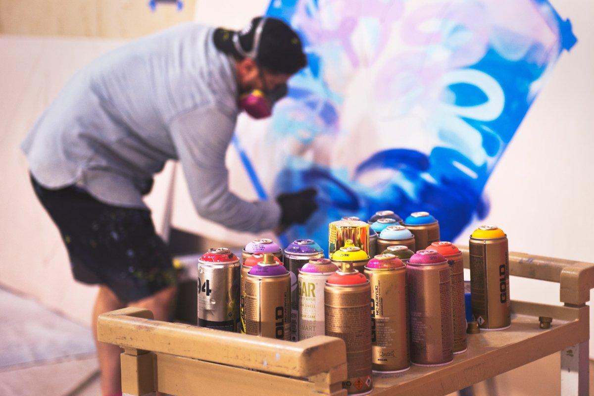 latas de pintura en aerosol sobre una mesa y detrás hombre con gorro pintando graffiti en un muro; convocatoria