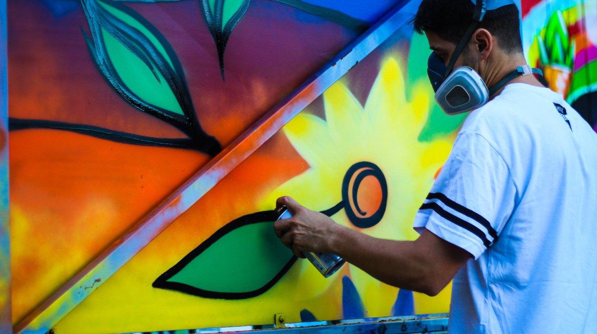 hombre con mascarilla en la cara pintando graffiti de flores de colores