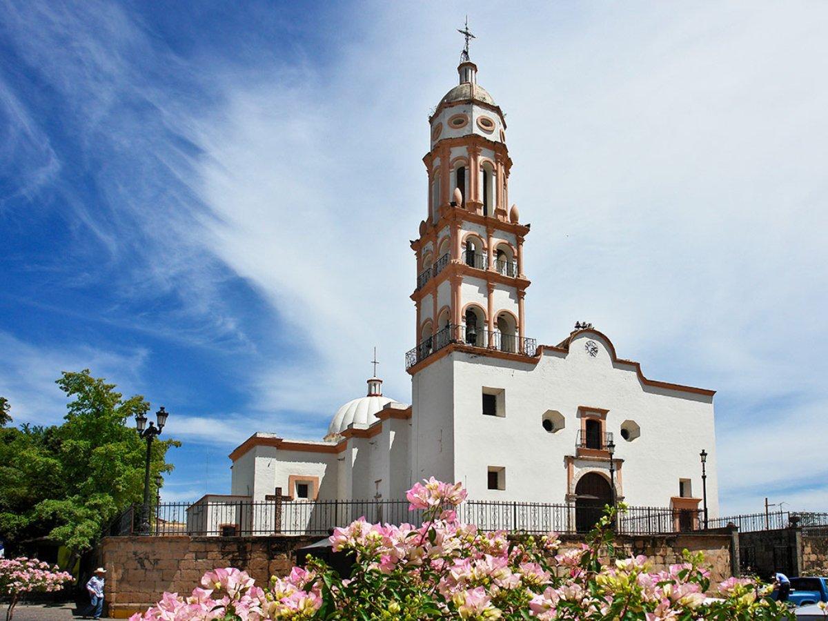 Iglesia color blanca con orillas color naranja. El cielo azul con nubes color blanco.