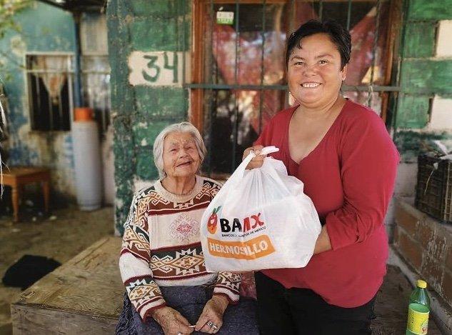 Señora con blusa color roja recibiendo una bolsa de despensa color blanca con letras color naranja que dice Hermosillo , a un lado una señora  mayor con un suéter con colores rojo, verde y crema
