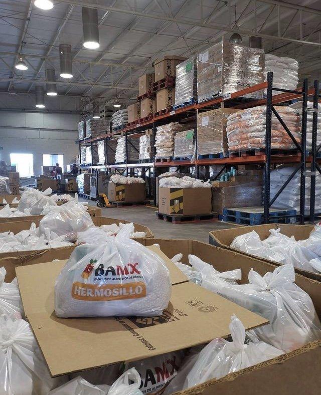 Almacén lleno de productos alimenticios, delante se observan cajas llenas de bolsas color blanco