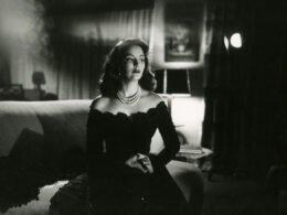 María Felix, la doña, vestida de negro y sentada en un sofá