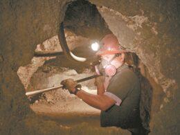 minero con casco naranja y linterna sostiene herramienta con las manos