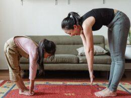 Del lado izquierdo: una niña con pantalon café claro y blusa color rosa. Del lado derecho: mujer con pantalon gris y blusa color negro. Las dos realizando estiramiento.