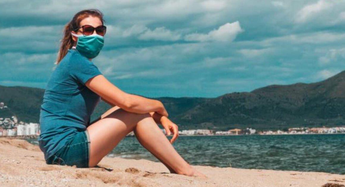 mujer con shorts y camiseta sentada sobre la arena en la playa viste un cubrebocas