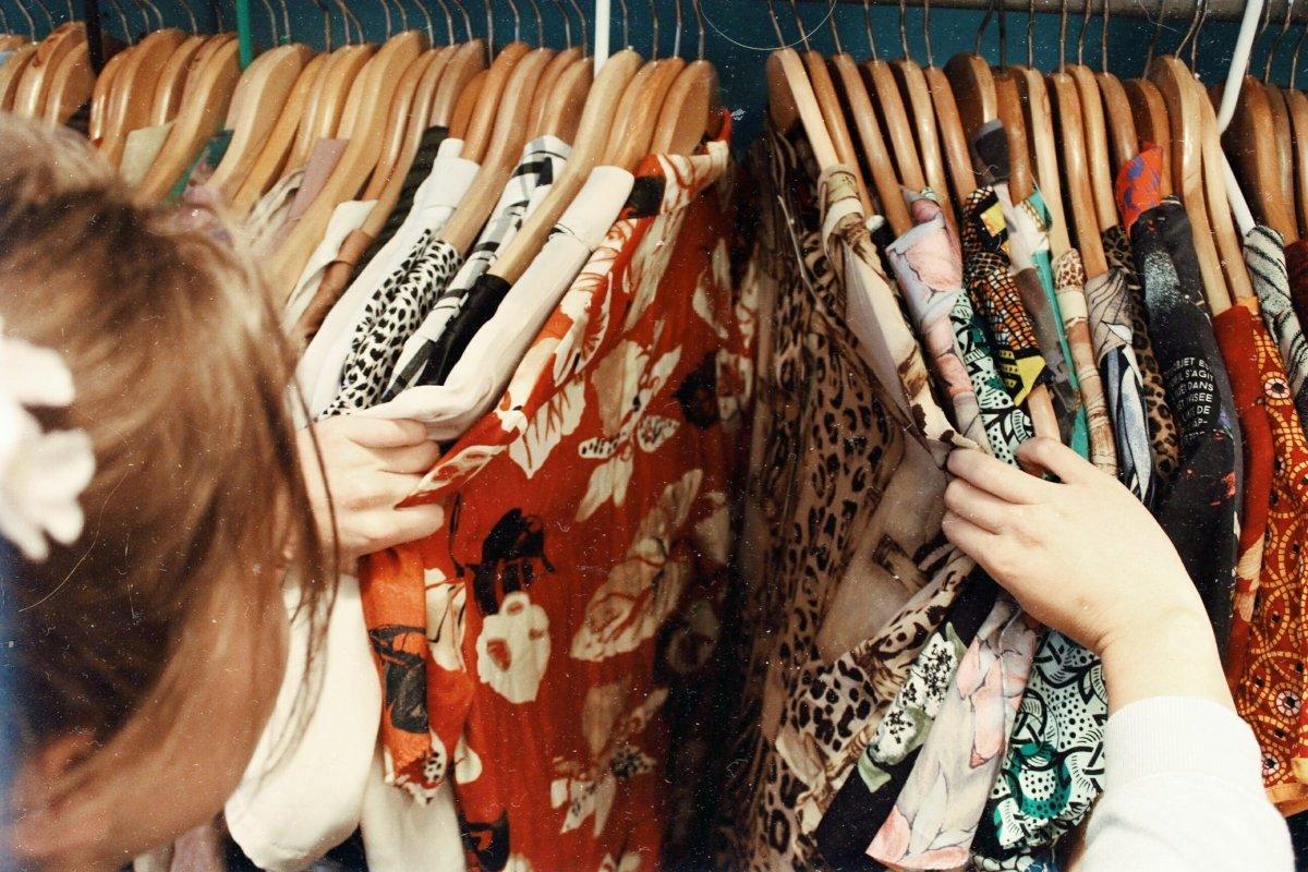 mujer viendo camisas estampadas de flores en una tienda