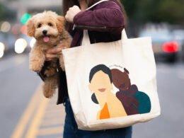 mujer sostiene a perro color cafe con el brazo derecho y una bolsa de tela cuelga de su hombro izquierdo