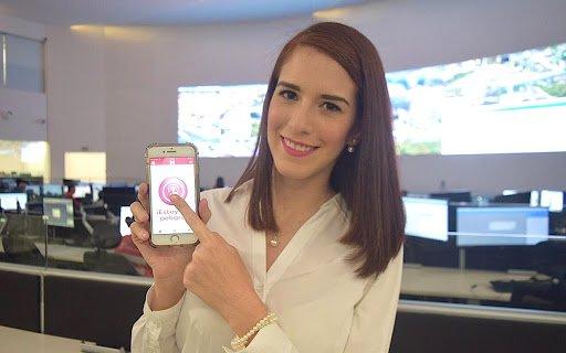 mujer de cabello lacio sonríe y sostiene un teléfono blanco mientras presiona la pantalla con su dedo índice; atrás hay monitores de computadoras