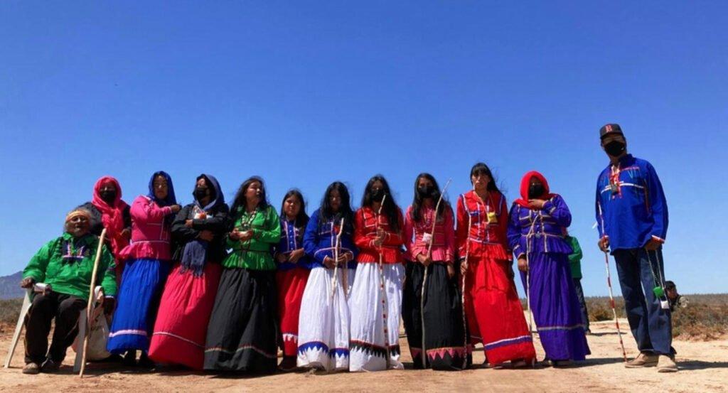 Grupo de 10 mujeres y 2 hombres seris. Las mujeres con falda larga, dos mujeres de en medio tienen una falda color blanca y blusa azul y roja.