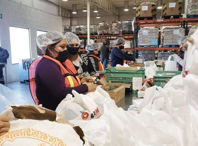 Señoras ayudando a empacar donaciones, con cofia color blanca, cubre bocas color negro y chaleco color naranja