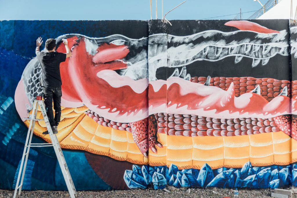 Luis Hinojosa en medio de la creación de un mural