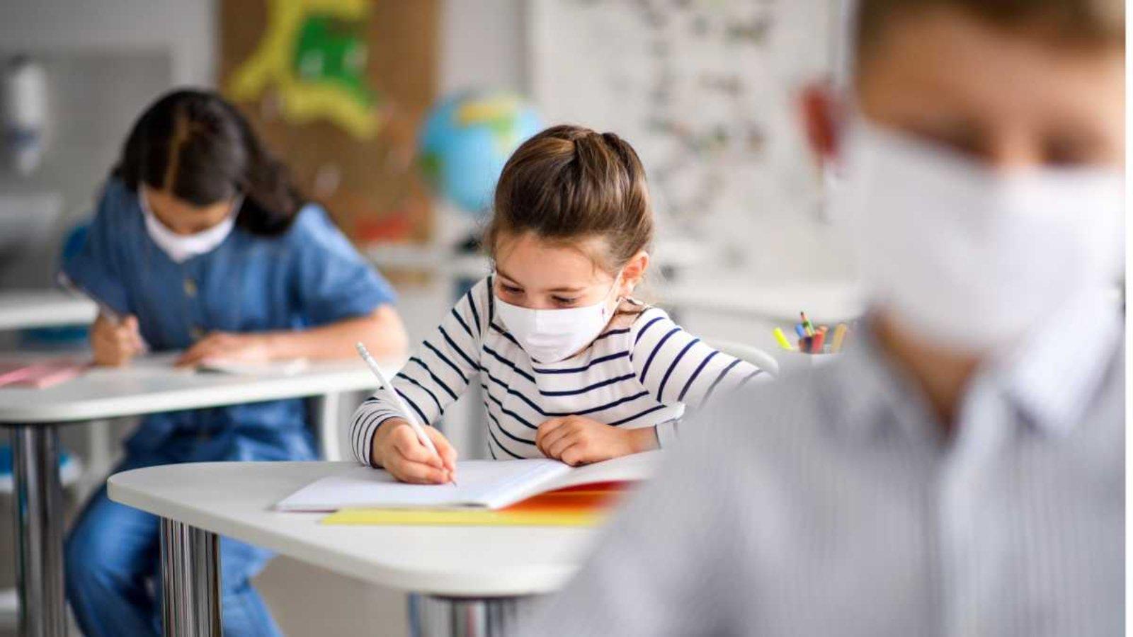 Niña con blusa de color blanca y rayas negras con cubreboca color blanco sentada en un mesa-banco escribiendo.