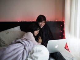pareja mirando peliculas en su cama