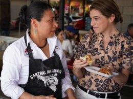 Dos chicas: la del lado derecho tiene una blusa color crema con flores color negro, en la mano un plato blanco con tacos de carne asada. La chica del lado izquierdo tiene una blusa color blanca y mandil color negro.