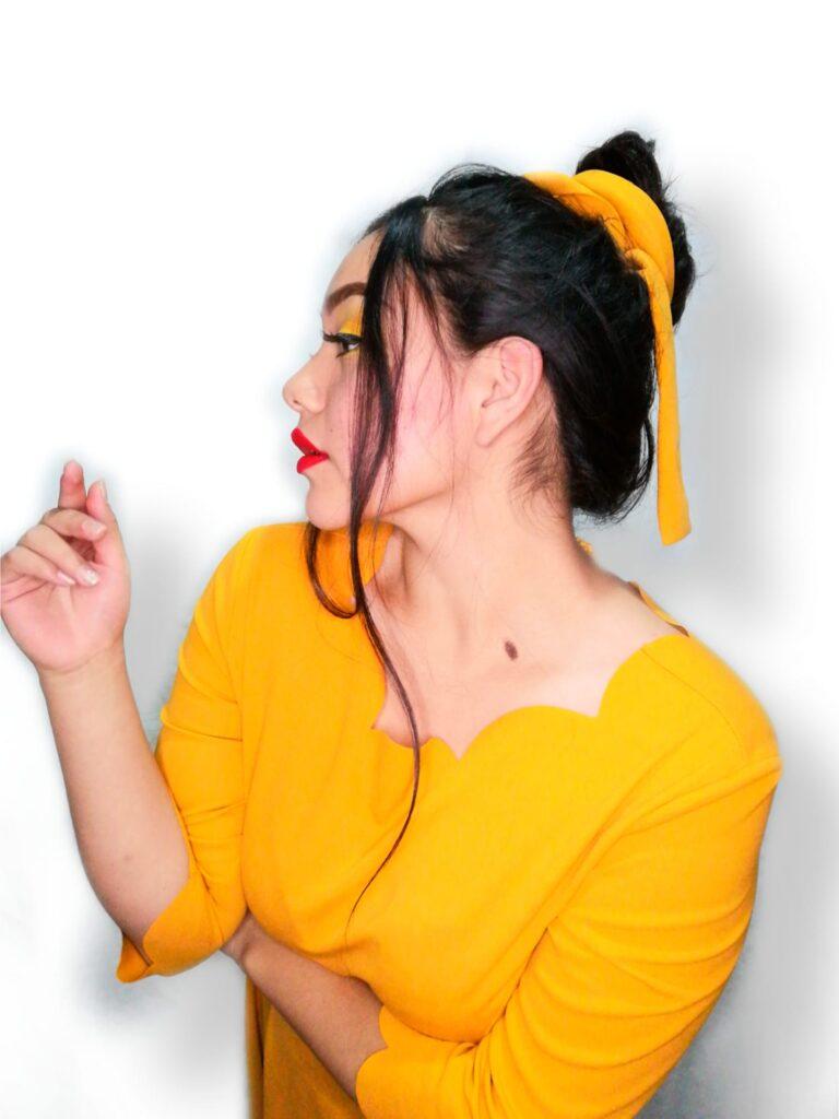 Anai Zúñiga de perfil con traje amarillo