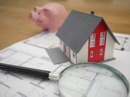 figura de casa miniatura, alcancía de cerdo y una lupa