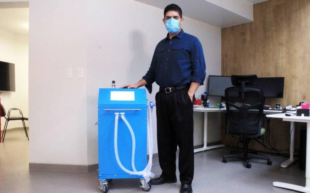Hombre con camisa color azul marino y pantalon de vestir color negro, junto a ventilador color azul.