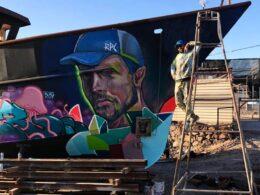 hombre sobre escalera al lado de un mural pintado en un barco varado