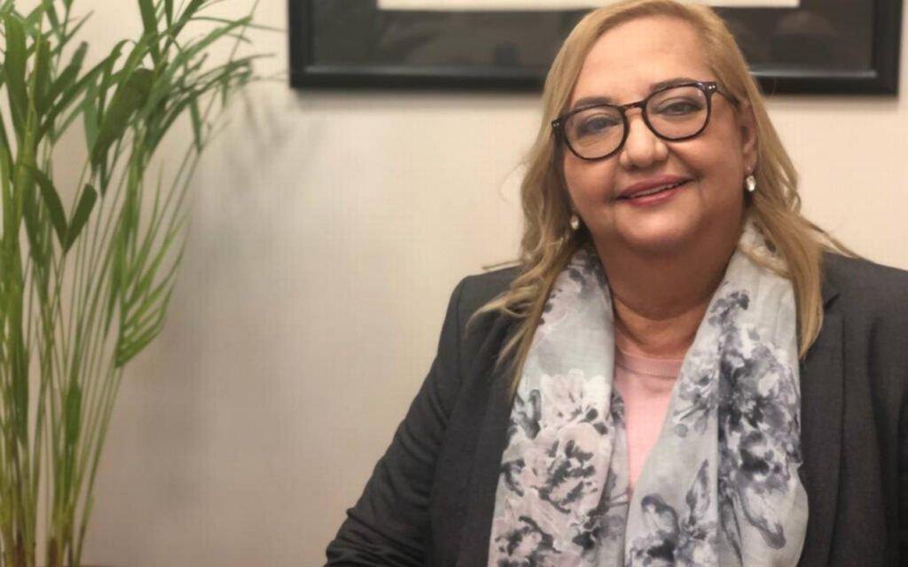 Rita en oficina de Unison, con un saco color gris oscuro, mascada con flores gris claro combinado con gris oscuro.