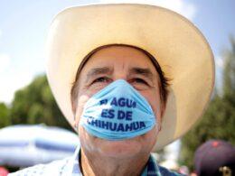 """Señor con sombrero color beige y cubrebocas azul que dice """"el agua es de Chihuahua"""""""