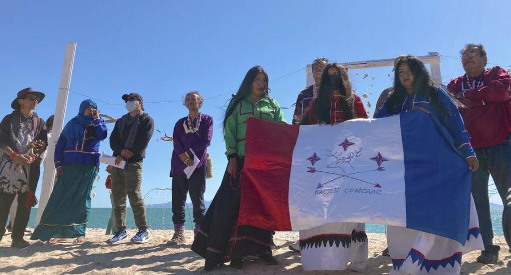 Tres mujeres seris con bandera de Nacion Comcaac de color rojo, blanco y azul. En medio de la bandera un venado con dos flechas y tres estrellas en la parte de arriba.