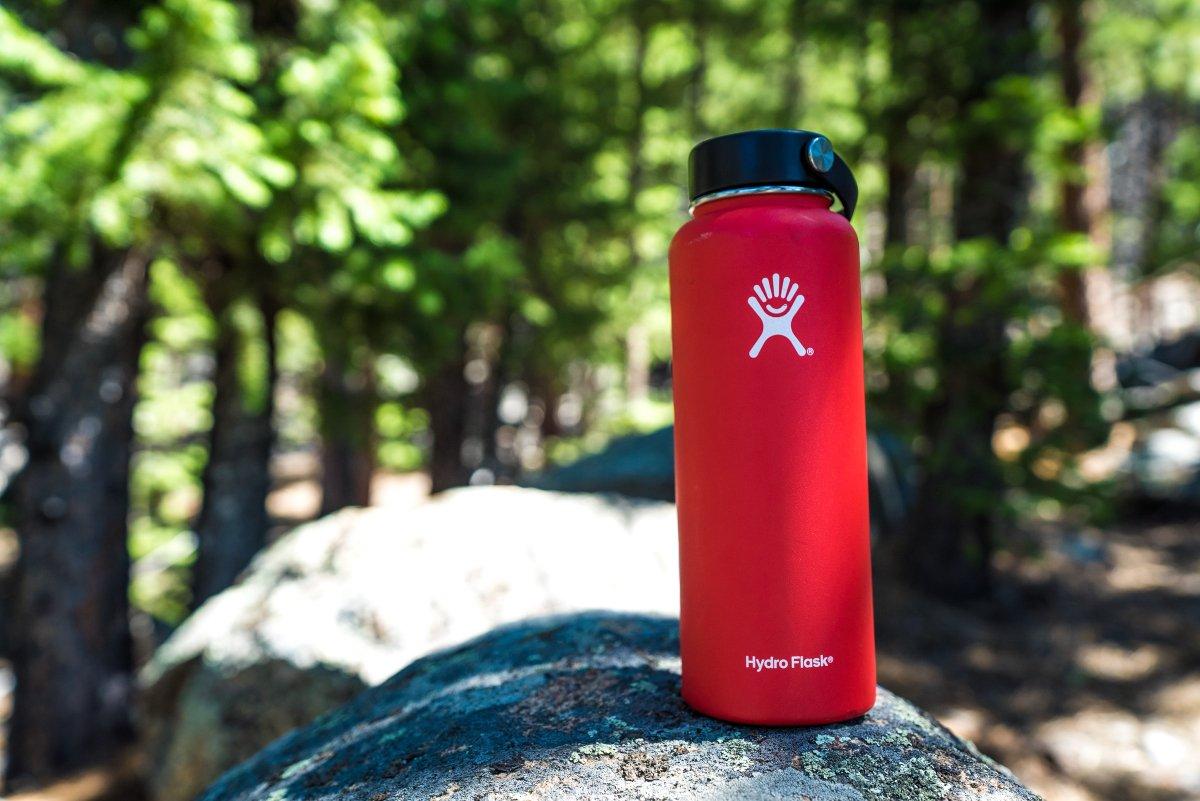 botella de agua roja con motivos blancos sobre una roca en el bosque; hábitos eco friendly