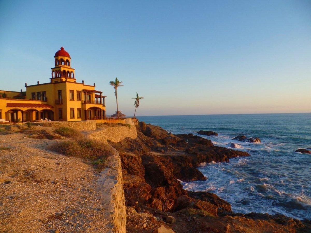 Todos Santos pueblo mágico del noroeste. Paisaje del mar en donde se encuentra un edificio del lado izquierdo color amarillo con rojo y una cúpula alta.