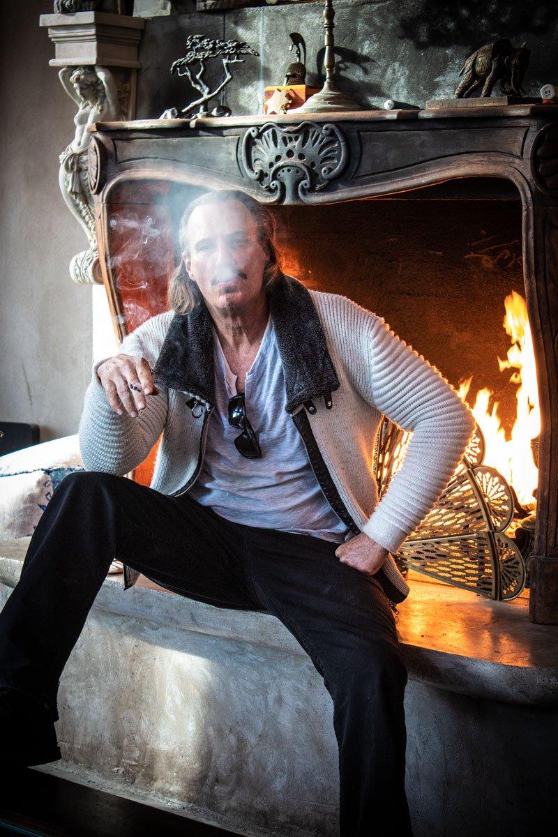 Hombre con chamarra color blanco con negro, pantalon negro, en la mano derecha un cigarrillo prendido y por la boca sacando humo, junto a chimenea.
