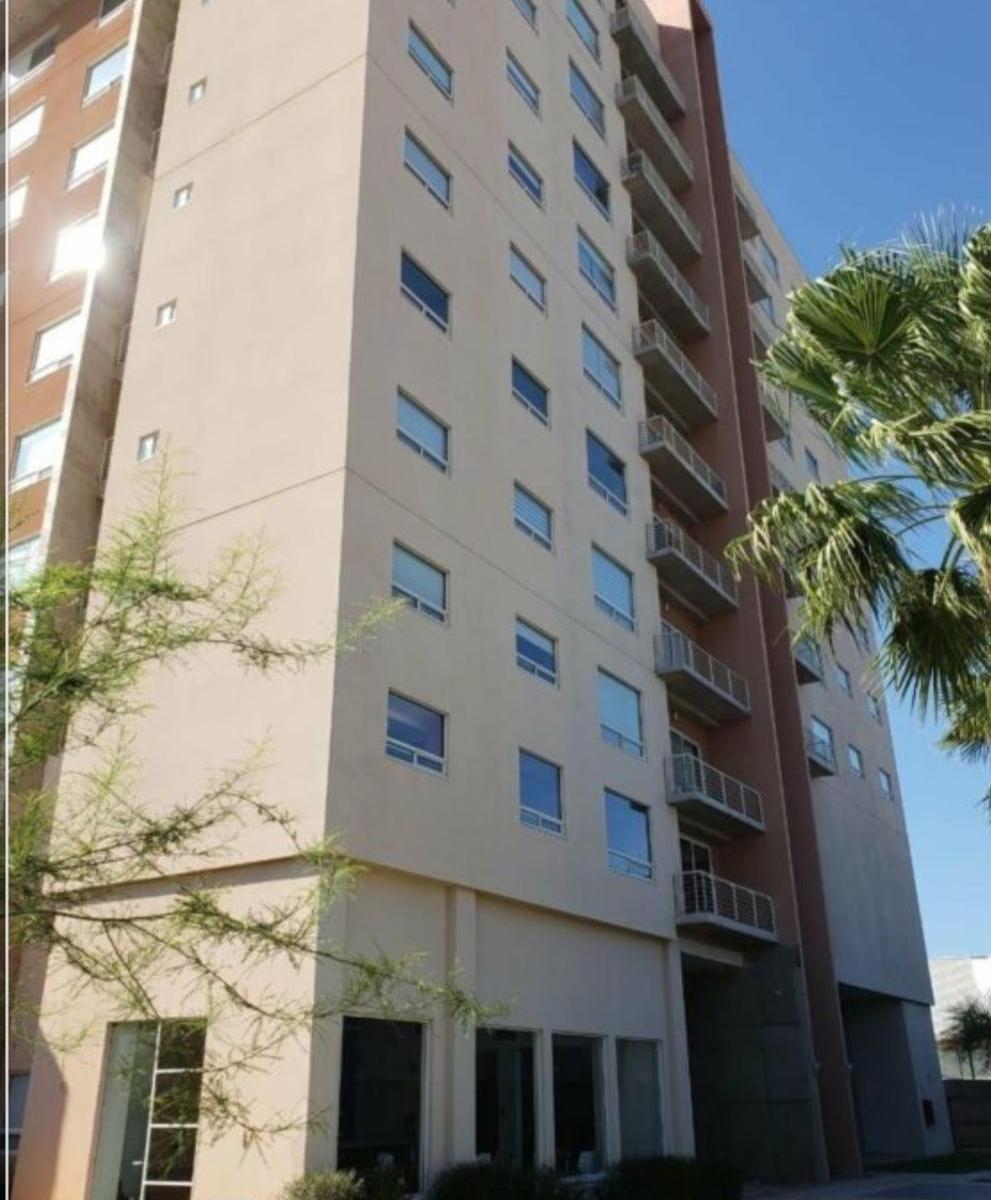 Edificio vertical en Hermosillo de color crema con naranja oscuro. Del lado derecho se ve una palma y del lado izquierdo un árbol de palo verde. Vivir vertical