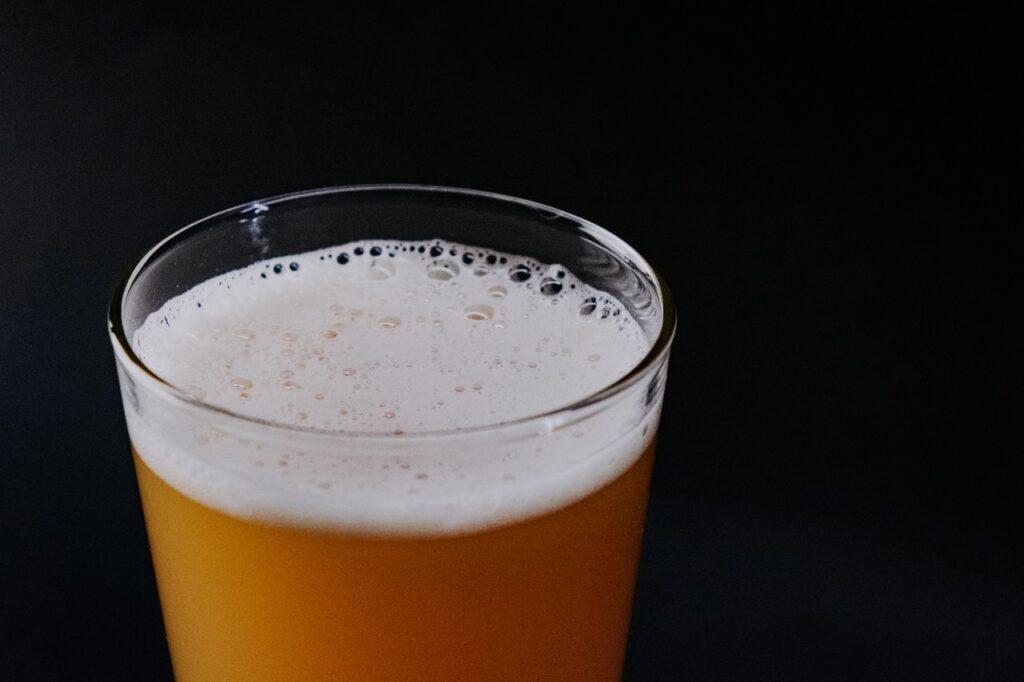 Vaso de cerveza clara, fondo negro