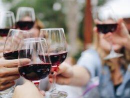 personas brindando con copas de vino tinto